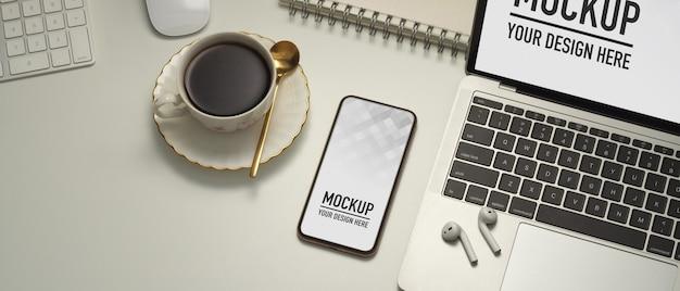 Perto da área de trabalho com maquete de smartphone, laptop, xícara de café e acessórios