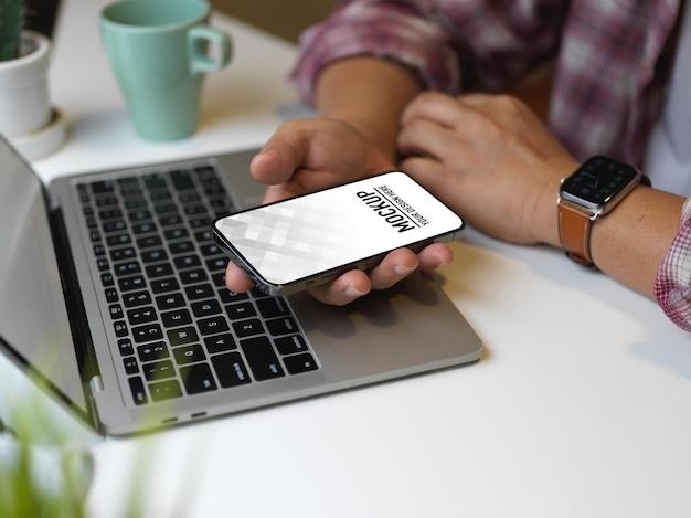 Perto da mão do empresário usando a maquete do smartphone