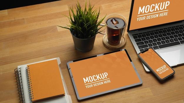 Perto da mesa de madeira com tablet, smartphone, maquete de laptop