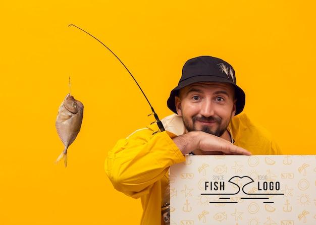 Pescador em modelo de capa de chuva e peixe