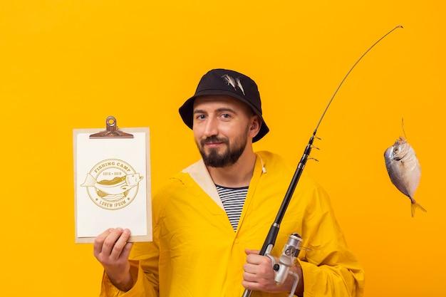 Pescador na capa de chuva com peixe troféu na haste