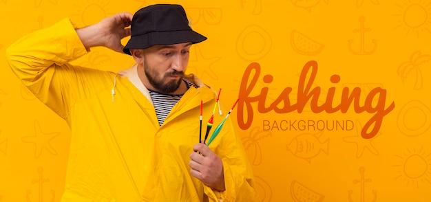 Pescador na capa de chuva e maquete de chapéu