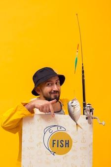 Pescador na capa de chuva, segurando a haste com peixe