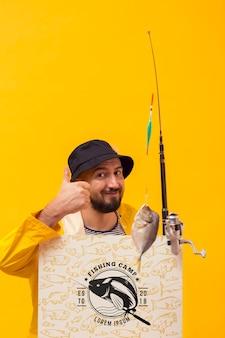 Pescador na capa de chuva, segurando a haste