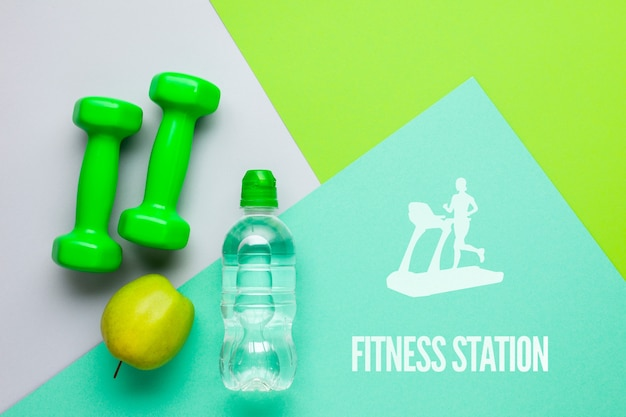 Pesos de fitness com garrafa de água e maçã