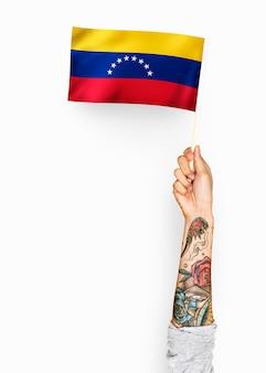 Pessoa acenando a bandeira da república bolivariana da venezuela