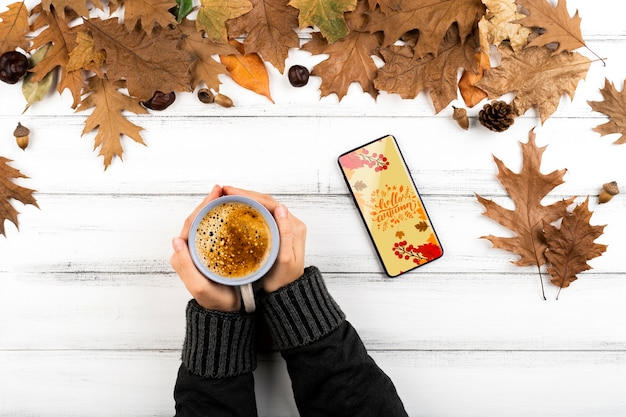 Pessoa de close-up com café e smartphone