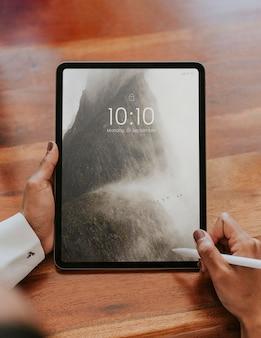 Pessoa de negócios usando uma caneta sem fio com uma maquete de tablet digital em uma reunião