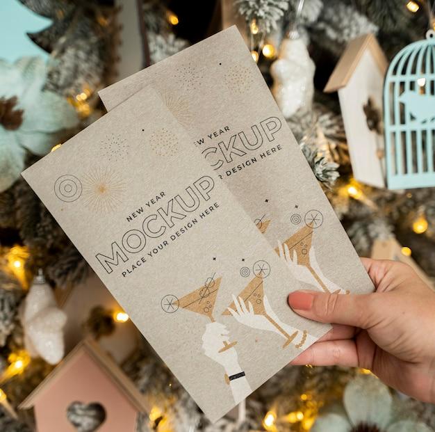 Pessoa segurando cartões mock-up na frente de decorações de natal