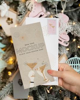 Pessoa segurando o cartão com o envelope ao lado dos enfeites de natal