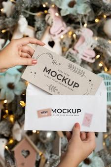 Pessoa segurando o cartão com um envelope ao lado das decorações de natal