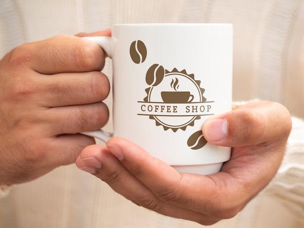 Pessoa, segurando uma xícara de café