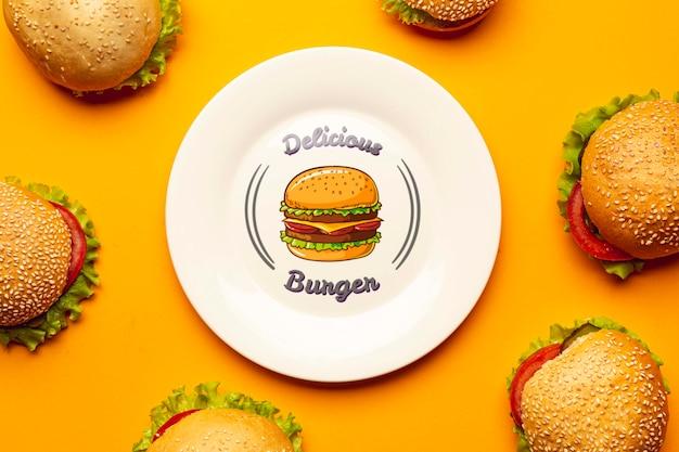 Placa de mock-up cercada por deliciosos hambúrgueres