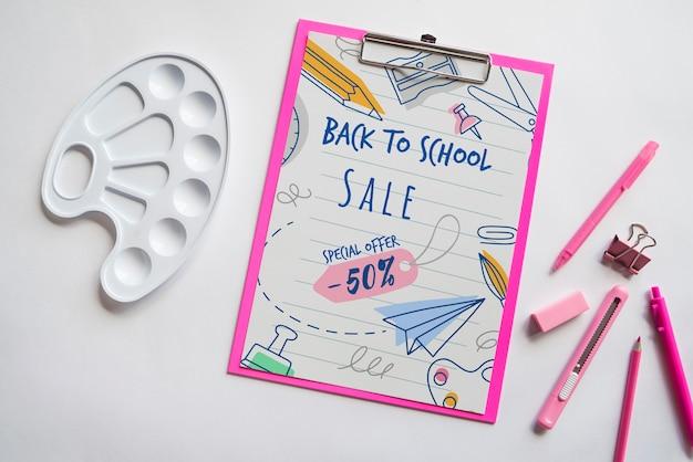 Plano de volta à venda da escola com prancheta e suprimentos