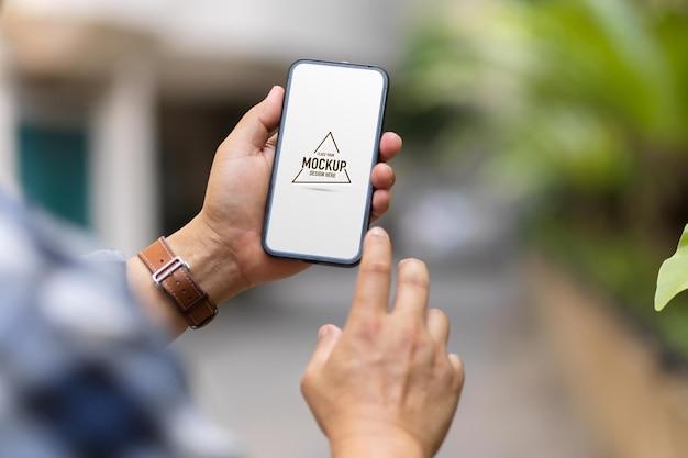 Por cima do ombro, close-up vista de um homem usando maquete de smartphone