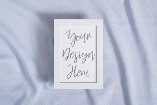 Porta-retrato com maquete de cartão de papel em branco em tecido de cor neutra azul