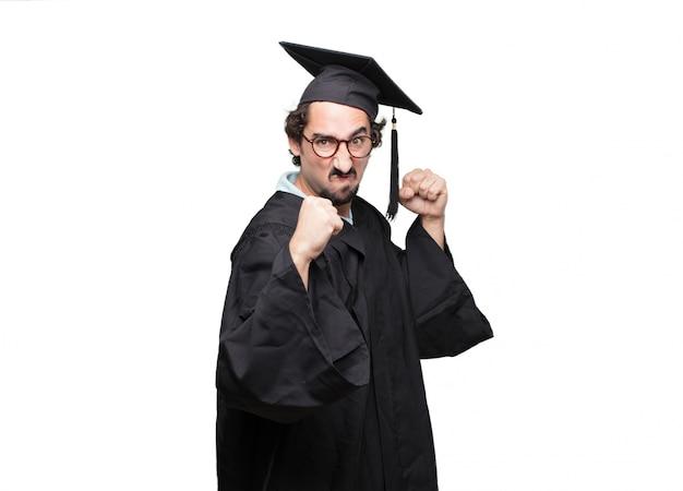 Pós-graduação homem barbudo com uma pose de raiva, agressivo e ameaçador, pronto para a luta, mostrando os punhos