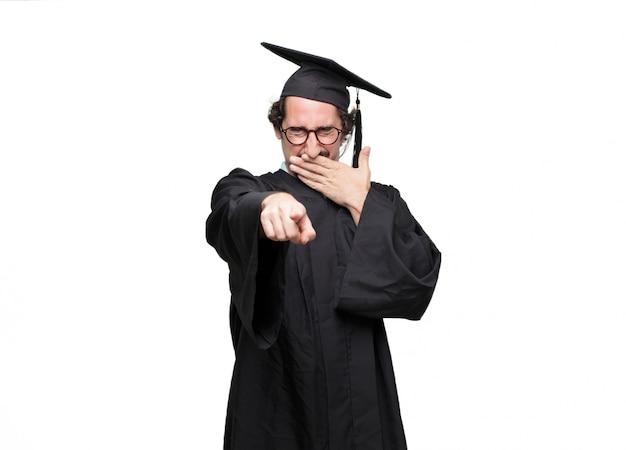 Pós-graduação homem barbudo rindo duro em algo hilário e apontando para o lado enquanto cobrindo a boca