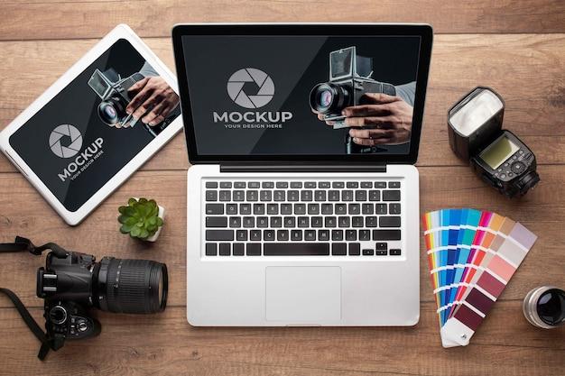 Posição plana da área de trabalho de madeira do fotógrafo com laptop