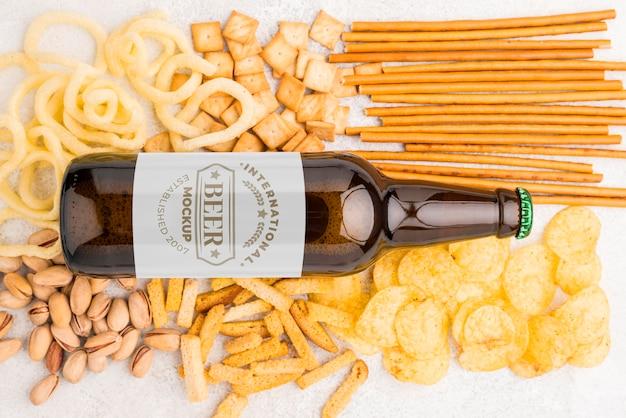 Posição plana da garrafa de cerveja com variedade de lanches