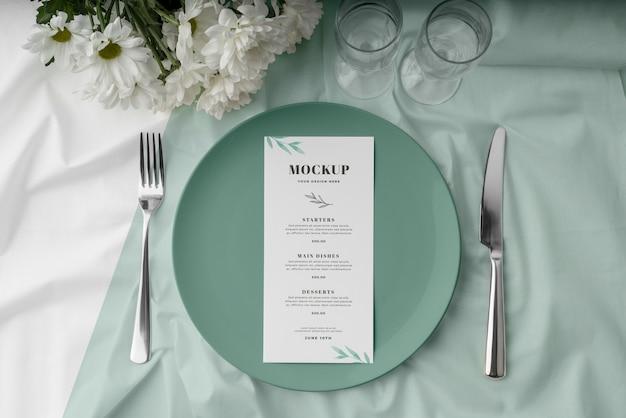 Posição plana da maquete do menu de primavera no prato com talheres e copos