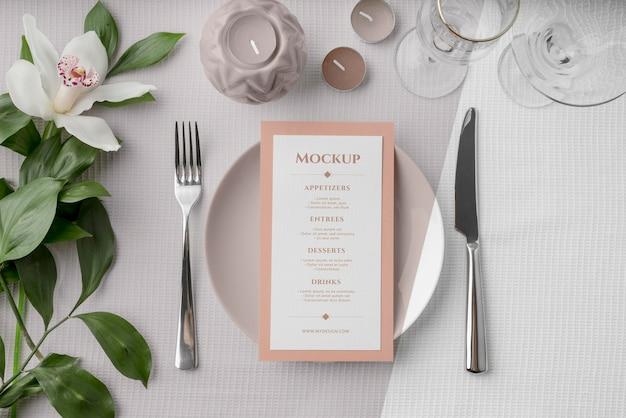 Posição plana da maquete do menu de primavera no prato com talheres e flores