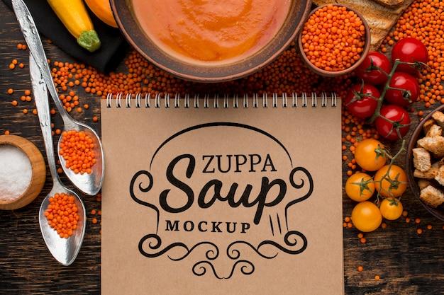 Posição plana da tigela de sopa com o caderno
