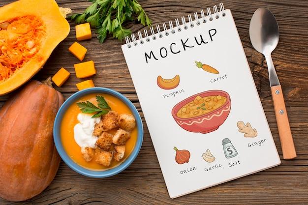 Posição plana da tigela de sopa de legumes com o caderno