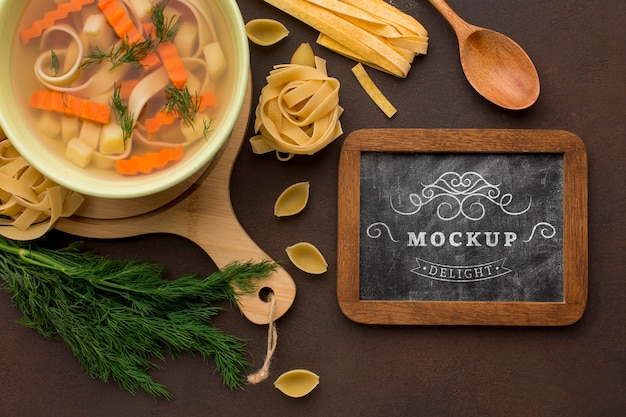 Posição plana do quadro-negro com tigela de sopa