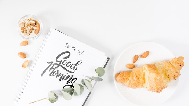 Postura plana de caderno ao lado de croissant