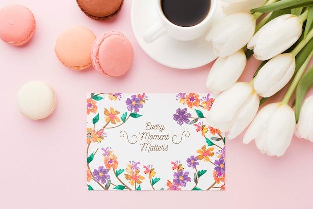 Postura plana de cartão com macarons e tulipas
