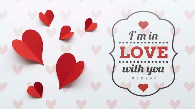 Postura plana de corações de papel com mensagem de amor