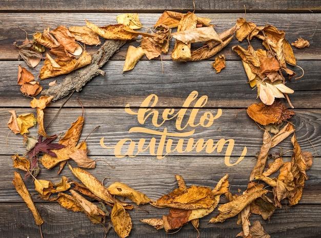 Postura plana de folhas de outono na mesa de madeira