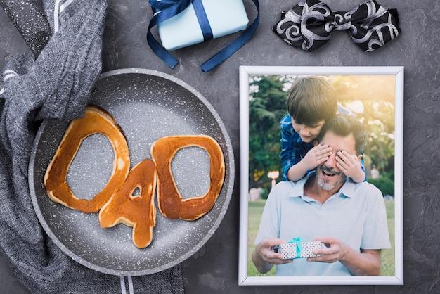 Postura plana de foto com panquecas na panela e presente para o dia dos pais