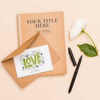 Postura plana de livro com flor e cartão