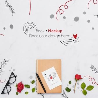Postura plana de livro com rosas e óculos
