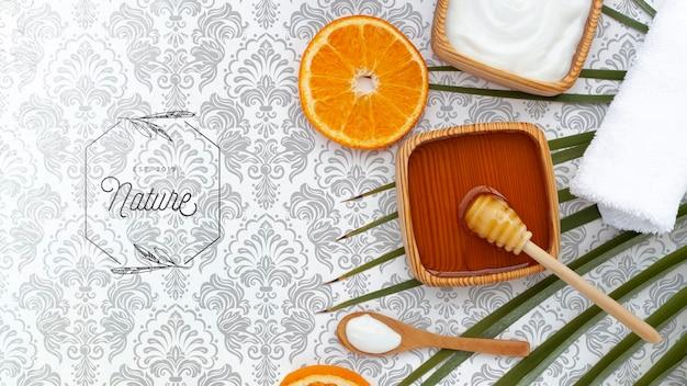 Postura plana de manteiga corporal e mel com fatia de laranja