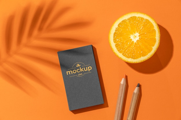 Postura plana de papelaria de papel com lápis e frutas cítricas