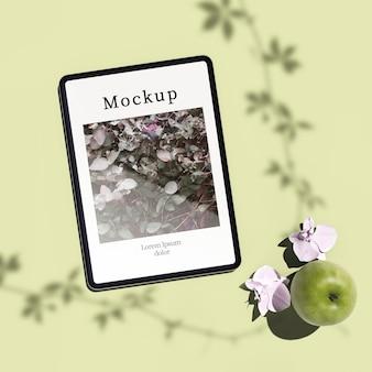 Postura plana de tablet com maçã e flores