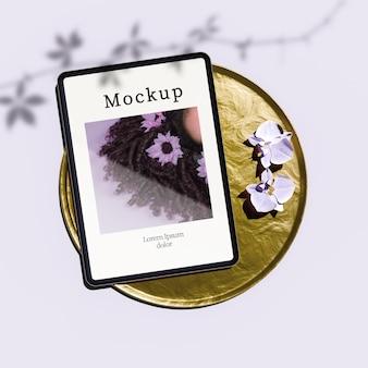 Postura plana de tablet na bandeja dourada com flores