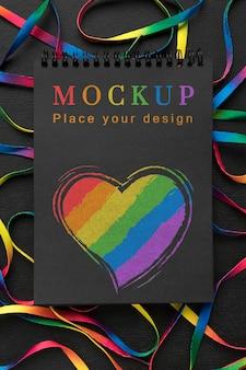 Postura plana do caderno com coração de arco-íris para diversidade