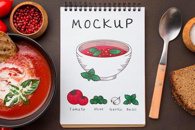 Postura plana do caderno com tigela de sopa