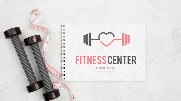 Postura plana do caderno de fitness com pesos e fita métrica