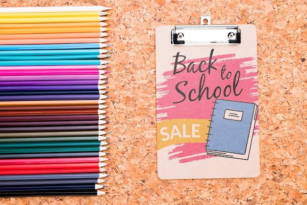 Prancheta ao lado de lápis coloridos mock-up