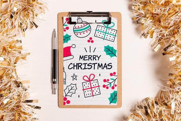 Prancheta de maquete de feliz natal e enfeites de ouro
