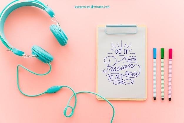 Prancheta, fones de ouvido e canetas