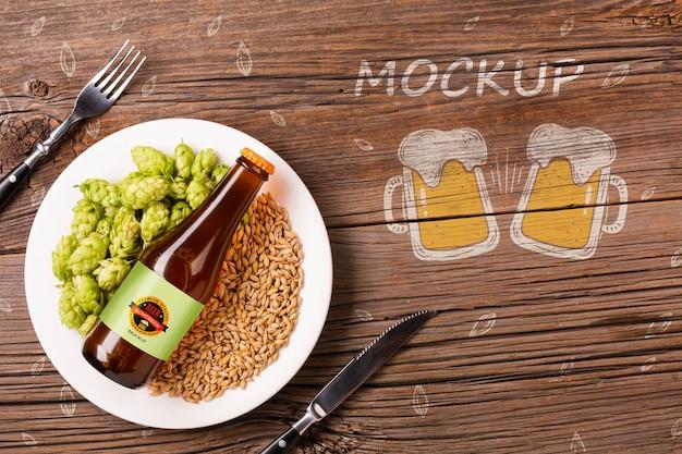 Prato com ingredientes de cerveja e garrafa de cerveja