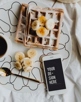 Prato de waffle com fatias de banana e uma xícara de café ao lado de um smartphone