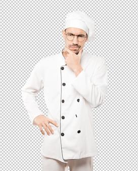 Preocupado jovem chef fazendo um gesto de dúvida
