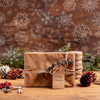 Presente de papel embrulhado com etiqueta e flocos de neve